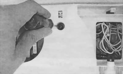 Отворачивают винты на задней панели
